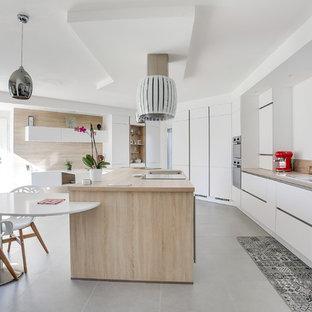 マルセイユの広いコンテンポラリースタイルのおしゃれなキッチン (ドロップインシンク、フラットパネル扉のキャビネット、白いキャビネット、木材カウンター、ベージュキッチンパネル、木材のキッチンパネル、黒い調理設備、グレーの床、ベージュのキッチンカウンター) の写真