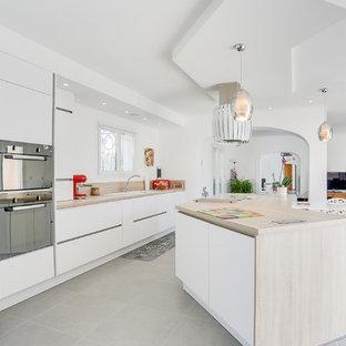 Aménagement d'une cuisine ouverte parallèle scandinave avec un évier posé, un placard à porte plane, des portes de placard blanches, un plan de travail en bois, un électroménager noir, un îlot central, un sol gris et un plan de travail beige.
