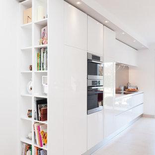 Idées déco pour une grand cuisine linéaire et beige et marron contemporaine avec des portes de placard blanches, une crédence grise, un placard à porte affleurante, un plan de travail en quartz, une crédence en dalle métallique et un électroménager encastrable.
