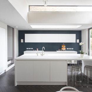 Cette image montre une cuisine américaine design avec un évier 1 bac, un placard à porte plane, des portes de placard blanches, un électroménager en acier inoxydable, un sol en bois foncé, un îlot central et un sol marron.