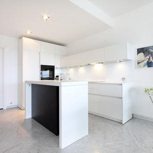 Cette image montre une cuisine ouverte parallèle minimaliste de taille moyenne avec des portes de placard blanches, un électroménager encastrable, un sol en marbre et un îlot central.