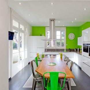 Aménagement d'une grande cuisine américaine contemporaine en L avec un évier encastré, des portes de placard blanches, un électroménager encastrable, un sol en carrelage de céramique et un îlot central.