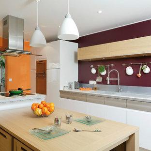 Idée de décoration pour une cuisine parallèle design fermée et de taille moyenne avec des portes de placard blanches, une crédence blanche, un électroménager en acier inoxydable et un îlot central.