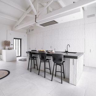 Exemple d'une grande cuisine ouverte linéaire bord de mer avec des portes de placard blanches, un plan de travail en granite, un sol en carrelage de céramique, un îlot central, un plan de travail noir, un évier 1 bac, un placard à porte plane et un sol blanc.