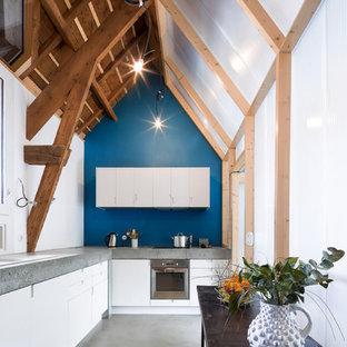Inspiration pour une cuisine américaine design en L de taille moyenne avec un évier posé, un placard à porte plane, des portes de placard blanches, un électroménager en acier inoxydable, béton au sol, un plan de travail en béton, une crédence bleue et aucun îlot.