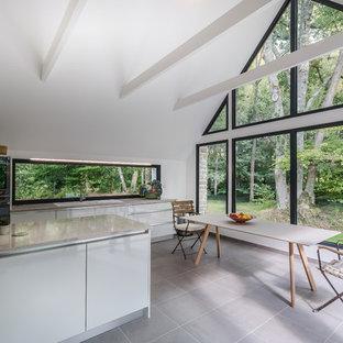 Idée de décoration pour une cuisine américaine parallèle design de taille moyenne avec un évier encastré, un placard à porte plane, des portes de placard blanches, un plan de travail en inox, une crédence en fenêtre et un îlot central.