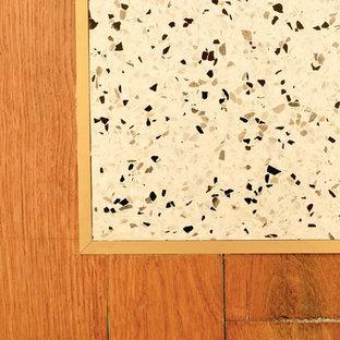 Imagen de cocina de galera, bohemia, pequeña, abierta, con fregadero bajoencimera, puertas de armario grises, encimera de madera, salpicadero gris, salpicadero de azulejos de terracota, electrodomésticos negros, suelo de terrazo, una isla y suelo blanco