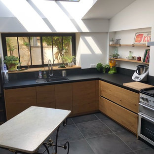 Design ideas for a large industrial u-shaped separate kitchen in Bordeaux with a single-bowl sink, light wood cabinets, laminate benchtops, black splashback, slate splashback, stainless steel appliances, no island, grey floor and black benchtop.