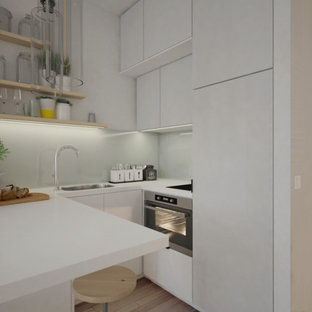 This is an example of a small contemporary u-shaped eat-in kitchen in Paris with an integrated sink, beaded inset cabinets, white cabinets, laminate benchtops, white splashback, glass tile splashback, stainless steel appliances, light hardwood floors, no island, brown floor and white benchtop.