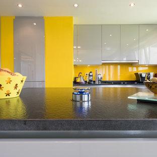 パリの中くらいのエクレクティックスタイルのおしゃれなキッチン (一体型シンク、インセット扉のキャビネット、グレーのキャビネット、御影石カウンター、黄色いキッチンパネル、ガラスタイルのキッチンパネル、シルバーの調理設備) の写真