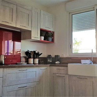 This is an example of a mid-sized midcentury l-shaped separate kitchen in Other with a farmhouse sink, beaded inset cabinets, distressed cabinets, laminate benchtops, red splashback, mirror splashback, stainless steel appliances, laminate floors, no island, brown floor and brown benchtop.