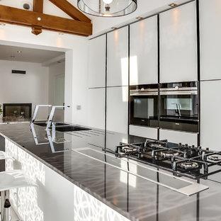 Idées déco pour une cuisine américaine linéaire contemporaine de taille moyenne avec un évier encastré, un placard à porte plane, des portes de placard blanches, un électroménager blanc et un îlot central.