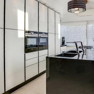 Aménagement d'une grande cuisine américaine linéaire contemporaine avec un évier encastré, un placard à porte plane, des portes de placard blanches, un électroménager blanc et un îlot central.