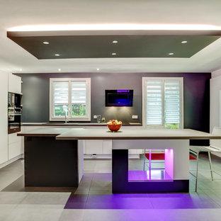 Exemple d'une cuisine américaine tendance en L de taille moyenne avec un placard à porte plane, des portes de placard blanches, une crédence grise et un îlot central.