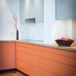 Cette image montre une grande cuisine design en L fermée avec des portes de placard oranges et aucun îlot.