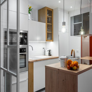 Design ideas for a small modern galley open plan kitchen in Paris with a single-bowl sink, white cabinets, soapstone benchtops, white splashback, subway tile splashback, panelled appliances, ceramic floors, with island, grey floor and brown benchtop.