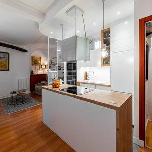 パリの小さいモダンスタイルのおしゃれなキッチン (シングルシンク、白いキャビネット、ソープストーンカウンター、白いキッチンパネル、サブウェイタイルのキッチンパネル、パネルと同色の調理設備、セラミックタイルの床、グレーの床、茶色いキッチンカウンター) の写真