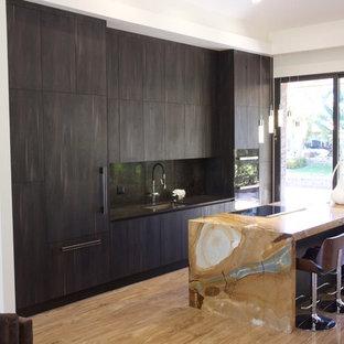 Idées déco pour une cuisine ouverte parallèle contemporaine de taille moyenne avec un évier encastré, un placard à porte affleurante, des portes de placard marrons, un plan de travail en quartz, une crédence marron, un électroménager encastrable, un sol en bois clair et un îlot central.