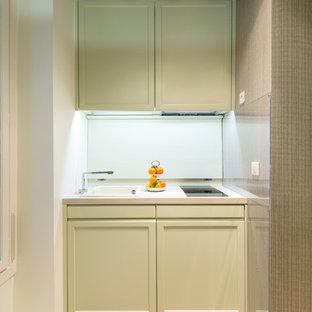 パリのトランジショナルスタイルのおしゃれなキッチン (アンダーカウンターシンク、インセット扉のキャビネット、緑のキャビネット、クオーツストーンカウンター、ベージュキッチンパネル、パネルと同色の調理設備、淡色無垢フローリング、アイランドなし、茶色い床、ベージュのキッチンカウンター) の写真