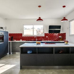 Réalisation d'une grand cuisine parallèle design avec des portes de placard grises, un plan de travail en stratifié, une crédence rouge, une crédence en carrelage métro, un électroménager en acier inoxydable, un sol en carrelage de céramique, un placard à porte plane et un sol gris.