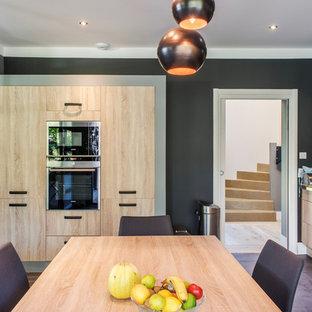 Idées déco pour une grande cuisine américaine linéaire contemporaine avec des portes de placard en bois clair, un électroménager en acier inoxydable, un sol en carrelage de céramique, aucun îlot et un placard à porte plane.