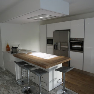 Inspiration for a mid-sized modern galley open plan kitchen in Marseille with an undermount sink, beaded inset cabinets, white cabinets, laminate benchtops, stainless steel appliances, marble floors, with island and grey floor.