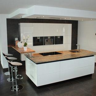 Idées déco pour une cuisine parallèle moderne de taille moyenne avec un évier intégré, un plan de travail en granite, un électroménager encastrable, un sol en ardoise et un îlot central.