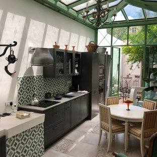 Inspiration for a large classic single-wall open plan kitchen in Marseille with a belfast sink, shaker cabinets, dark wood cabinets, granite worktops, green splashback, cement tile splashback, black appliances, cement flooring, beige floors and grey worktops.