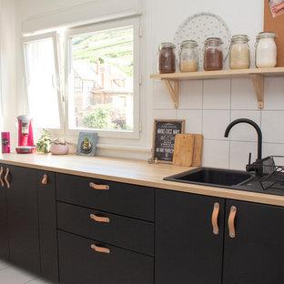 Idées déco pour une cuisine scandinave de taille moyenne avec un évier 1 bac, des portes de placard noires, une crédence blanche, un sol blanc, un placard à porte plane, un plan de travail en bois et un plan de travail beige.