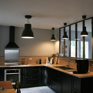 Inspiration for a large urban open plan kitchen in Bordeaux with an integrated sink, black cabinets, wood worktops, black splashback, wood splashback, stainless steel appliances, cement flooring, multiple islands and white floors.