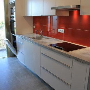 Diseño de cocina lineal, minimalista, pequeña, cerrada, sin isla, con fregadero de un seno, encimera de laminado, salpicadero rojo, salpicadero de azulejos de cerámica, electrodomésticos de acero inoxidable, suelo de baldosas de cerámica y suelo gris