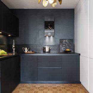 Inspiration pour une cuisine nordique en L avec un évier 1 bac, un placard à porte plane, des portes de placard noires, une crédence noire, un électroménager noir, un sol en bois clair et un plan de travail noir.