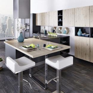 Exemple d'une grande cuisine ouverte tendance en L avec un îlot central, un évier encastré, un placard à porte plane, des portes de placard en bois clair, une crédence grise, un électroménager noir, un sol en bois foncé et un sol marron.