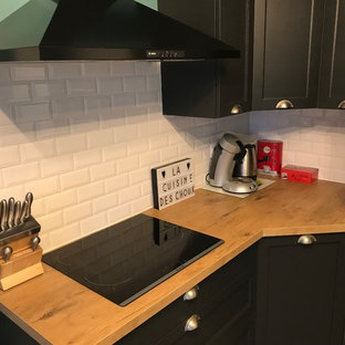 This is an example of a mid-sized midcentury l-shaped separate kitchen in Lille with a farmhouse sink, glass-front cabinets, dark wood cabinets, laminate benchtops, white splashback, subway tile splashback, white appliances, cement tiles, no island and grey floor.