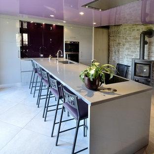 Неиссякаемый источник вдохновения для домашнего уюта: большая прямая кухня в современном стиле с обеденным столом, белыми фасадами и островом