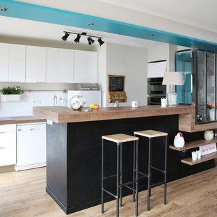 Aménagement d'une grand cuisine ouverte parallèle scandinave avec un placard à porte plane, des portes de placard blanches, une crédence blanche, un électroménager blanc, un sol en bois clair et une péninsule.
