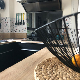 Inspiration for a mid-sized contemporary u-shaped open plan kitchen in Marseille with black cabinets, laminate benchtops, with island, a single-bowl sink, beaded inset cabinets, multi-coloured splashback, ceramic floors and pink floor.