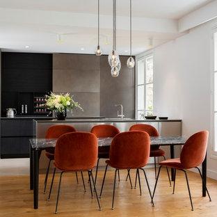 Diseño de cocina moderna, grande, abierta, con puertas de armario en acero inoxidable y suelo de madera clara