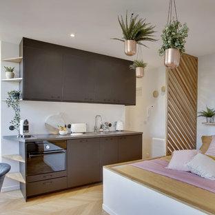 パリの小さいエクレクティックスタイルのおしゃれなキッチン (アンダーカウンターシンク、インセット扉のキャビネット、黒いキャビネット、ラミネートカウンター、白いキッチンパネル、黒い調理設備、淡色無垢フローリング、アイランドなし、ベージュの床、グレーのキッチンカウンター) の写真