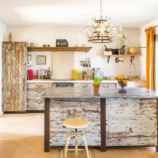 Photo of a mid-sized eclectic single-wall separate kitchen in Other with distressed cabinets, a drop-in sink, beaded inset cabinets, limestone benchtops, beige splashback, limestone splashback, stainless steel appliances, limestone floors, with island, beige floor and beige benchtop.