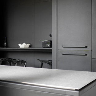 This is an example of a mid-sized contemporary l-shaped open plan kitchen in Lyon with an undermount sink, beaded inset cabinets, black cabinets, zinc benchtops, panelled appliances, concrete floors, with island, grey floor and grey benchtop.