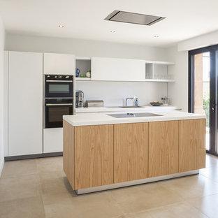 Cette image montre une cuisine design avec un placard à porte plane, des portes de placard blanches, une crédence blanche, un électroménager noir, un îlot central, un sol beige et un plan de travail blanc.