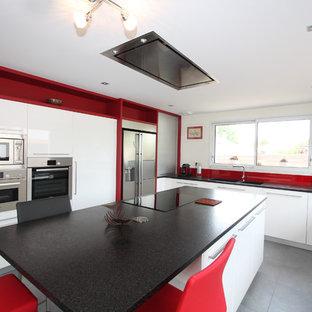 Cuisine moderne avec cuisson au centre et hotte de plafond.