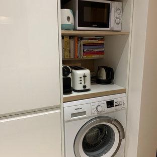 Exemple d'une cuisine ouverte linéaire chic de taille moyenne avec un évier encastré, un plan de travail en bois, un électroménager encastrable, aucun îlot, un sol beige, un plan de travail blanc et un plafond en papier peint.