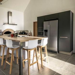 Réalisation d'une cuisine américaine nordique en L de taille moyenne avec des portes de placard blanches, un plan de travail en stratifié, une crédence en carreau de ciment, un électroménager en acier inoxydable et un îlot central.