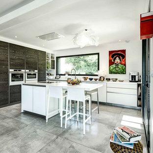 Aménagement d'une cuisine ouverte contemporaine en L avec un placard à porte plane, des portes de placard en bois sombre, un plan de travail en inox, une crédence blanche, un électroménager blanc, un îlot central, un sol gris et un plan de travail gris.