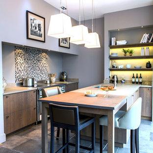 Cette image montre une cuisine parallèle design de taille moyenne avec un plan de travail en granite, une crédence en pierre calcaire, un sol en carrelage de céramique, une péninsule, un sol gris, un plan de travail beige, un évier encastré et une crédence grise.