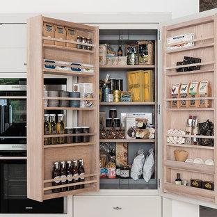 ナントの広いコンテンポラリースタイルのおしゃれなキッチン (アンダーカウンターシンク、フラットパネル扉のキャビネット、グレーのキャビネット、茶色いキッチンパネル、レンガのキッチンパネル、黒い調理設備、淡色無垢フローリング、ベージュの床) の写真
