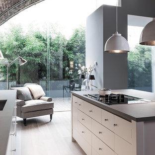 Foto de cocina de galera, contemporánea, grande, abierta, con salpicadero de piedra caliza, suelo de madera clara, una isla y suelo blanco
