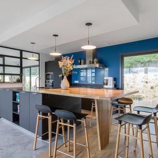 Exemple d'une grande cuisine ouverte parallèle tendance avec un évier intégré, un placard à porte plane, des portes de placard noires, un plan de travail en granite, béton au sol, un îlot central, un sol gris et un plan de travail noir.